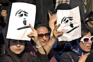 Iranian women hold banners during an Iranian Women Movement rally in front of Tehran University Sunday June 12, 2005. About 300 women took part in the protest against gender discrimination in the Islamic Republic. Image via AP.