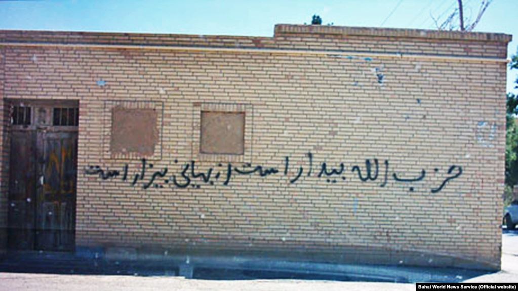 """An anti-Bahai graffiti on the wall of a building in the city of Abadeh says """"Hezbollah is awake and despises the Baha'is"""". FILE PHOTO"""